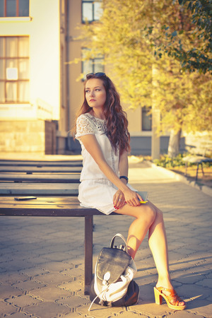 prose: Lovely girl hipster sitting on a bench in a white dress. Girl holding a book in her hands.