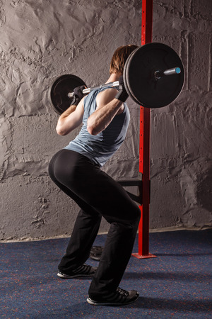 crouches: Man crouches with a barbell. Healthy lifestyle concept. Fitness club.