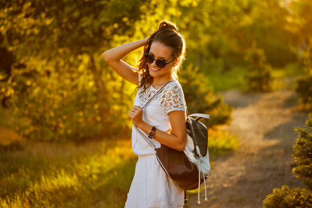 casual clothing: Lovely girl hippie walks in the park at sunset. Warm toning. Girl straightens her hair. Stock Photo