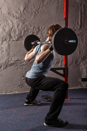 crouches: Man crouches down with a barbell. Healthy lifestyle concept. Fitness club.