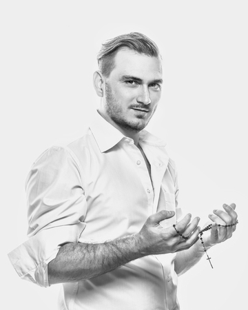 high key: Young romantic man in white shirt. Mens fashion. Man holds a rosary in his hands. Black and white photograph in a high key.