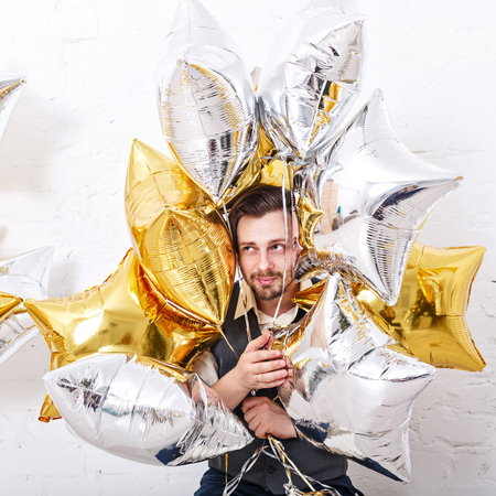 mens fashion: Young romantic man in the vest. Mens fashion. Man hiding in the balloons. Celebration.