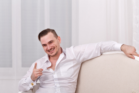 jokes: Young romantic man in white shirt. Mens fashion. Shirt with cufflinks. Man sitting on the couch and jokes.