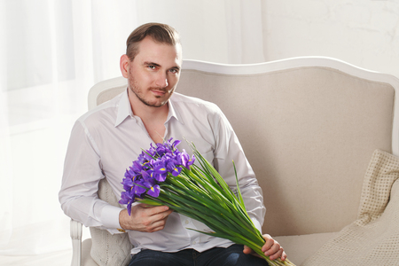 mens fashion: Young romantic man in white shirt. Mens fashion. A man holding a bouquet of spring flowers.