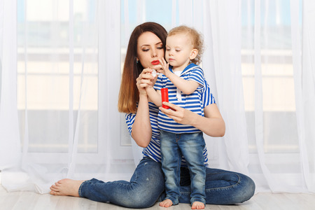inflate: Young mother and baby daughter inflate soap bubbles. Mother and daughter dressed in a striped t-shirt. Family joy Stock Photo