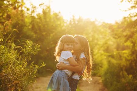Dos pequeñas hermanas hermosas gran abrazo y un beso en el parque en un día soleado de verano. Tiempo familiar. Niños lindos.