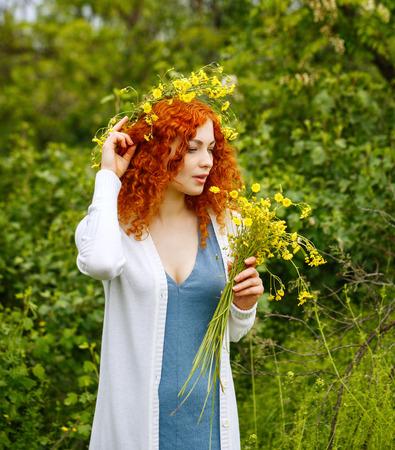 fleurs des champs: Jeune, séduisant, rouge, cheveux, femme tisse une couronne de fleurs sauvages. fille Hippie. L'unité avec la nature.