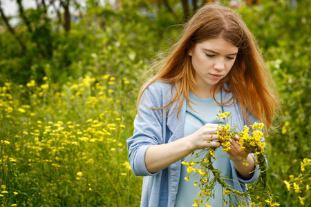 wildflowers: Young attractive woman weaves a wreath of wildflowers. Hippie girl. Unity with nature.