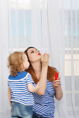 inflate: Young mother and little daughter inflate soap bubbles. Mother and daughter dressed in a striped t-shirt. Stock Photo