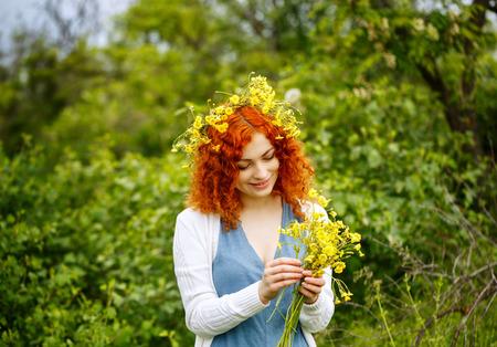 fiori di campo: Attraente giovane donna dai capelli rossi tesse una corona di fiori di campo. ragazza Hippie. L'unit� con la natura. Archivio Fotografico