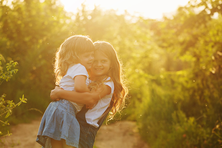 strongly: Two little sisters hugged strongly in park on a sunny summer day. Family time. Cute babies. Stock Photo