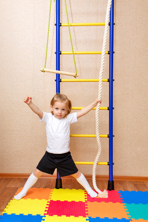 wall bars: Little girl posing next to the Wall bars. Sports Equipment. Childrens sports. Stock Photo