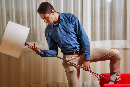 Businessman holding a floor lamp in his hand. Fooling around in the office, after complex negotiations. Chill out. Stock Photo