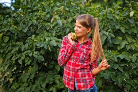 Young slim woman holding a green apple. Tasty and healthy snack. Raw food diet. Vegetarianism. Stock Photo