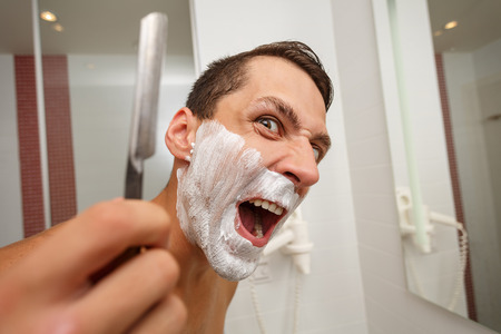 straight man: Man is holding a straight razor. Mad man. On the face of shaving cream.
