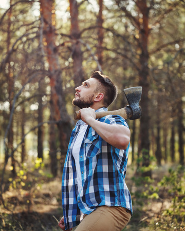 Lumberjack holding an ax. Woodcutter in plaid shirt chooses a tree. Felling trees. Logging. Manual labor.