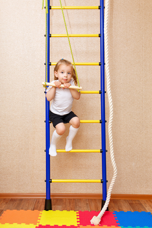 wall bars: A little girl clings to the bar. Wall bars. Sports Equipment. Childrens sports.