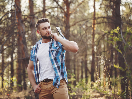 woodcutter: Lumberjack holding an ax on his shoulder. Woodcutter in plaid shirt chooses a tree. Felling trees. Logging. Manual labor.