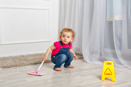 Little girl is cleaned with a mop in her hands. Little helper. Household chores. Stock Photo