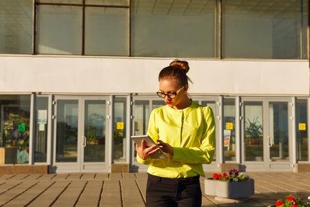 correspondence: La muchacha lleva a cabo la correspondencia de negocios en el Tablet PC al aire libre. Mujer de negocios en vidrios. ropa de estilo de negocios.