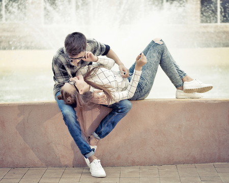 Sweethearts teenagers hug. Girlfriend and boyfriend hugging. They wear glasses. Warm toning. First love. He falls in love. Date. Stock Photo