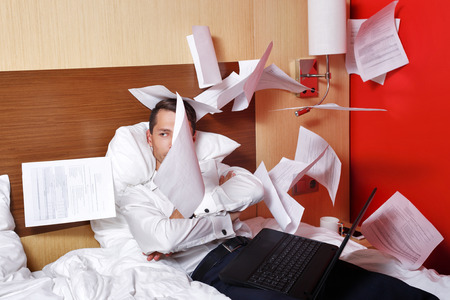 job deadline: The hell with the job. Businesswoman throws documents. Man with laptop sitting on the couch with his arms crossed, and fly papers around him. Deadline. Eff it!
