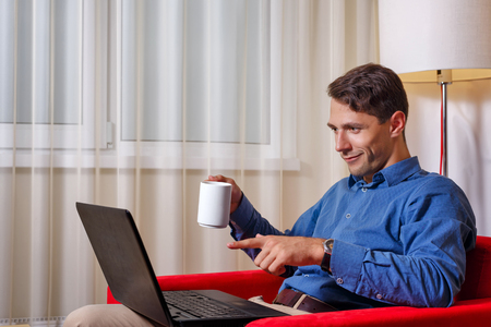 search result: Man works for laptop. He rejoices in the search result. A man holding a cup of coffee. Gambling. Stock Photo