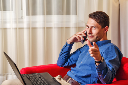 important phone call: Man works for laptop. Businessman discussing on a cell phone call details of important transactions and shows the index finger at the camera. Freelancer at work. I choose you.