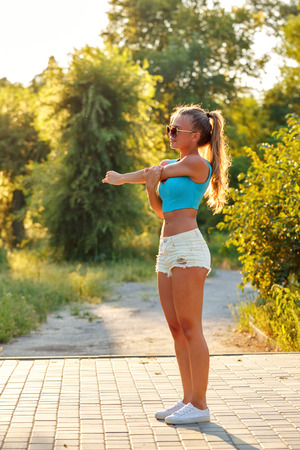 girdle: Young slim woman doing stretching humeral girdle in a city park. Outdoors Sports. Healthy lifestyle concept. Morning exercises