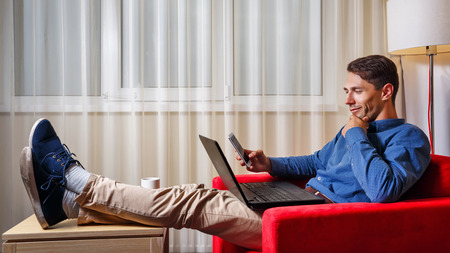 looking for work: Man works for laptop. Businessman looking thoughtfully at the laptop screen and the phones screen. Freelancer at work. Difficult choice.