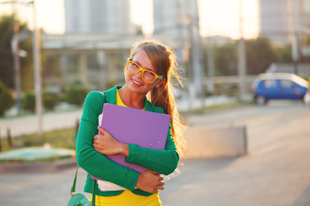 Business girl with a folder in her hands. Girl in glasses and jacket smiles. Stock Photo