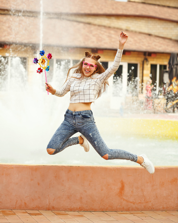 spinner: Lovely cheerful girl teenager jumping from a Spinner Array Tool. Summer holidays.