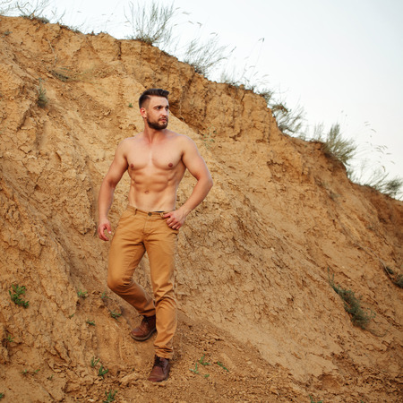 sand pit: Young handsome man descends into a sand pit. Muscular man with a fashionable hair and beard. Stock Photo
