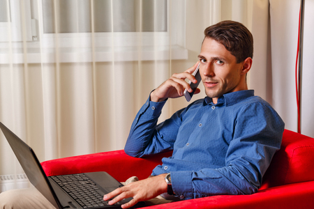 important phone call: Man works for laptop. Businessman discussing on a cell phone call details of important transactions. Freelancer at work. Life is good.