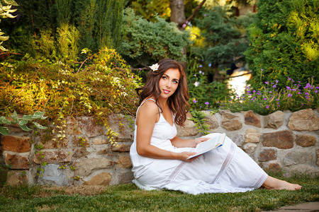 Lovely girl reading a book in the backyard. She in a long white dress sitting on the lawn. Reading outdoors air. Self-education.
