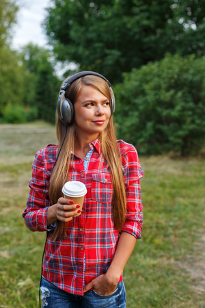 plaid shirt: Young girl in a plaid shirt listening to music on headphones and drinking morning coffee. Hipster rest.