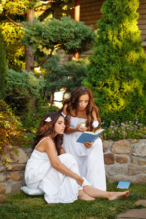 Two cute sisters reading a book in the backyard. Reading the open air. Self-education.