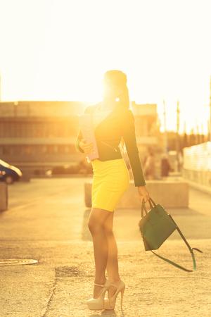 cerrando negocio: Mujer atractiva joven que recorre en una playa de estacionamiento en los rayos del sol poniente. Negocios la celebración de una carpeta con documentos y un bolso de moda. Piernas largas y zapatos de tacón alto. Una exitosa y positiva. Enfoque suave. Foto de archivo