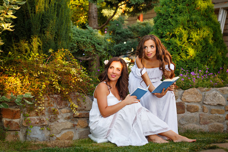 Two cute sisters reading books in the backyard. Girls in long white dresses. Reading the open air. Self-education.