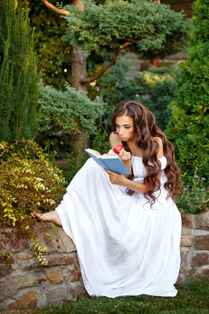 enthusiasm: Lovely girl with enthusiasm reads the interesting book. She holding a book and an apple in his hand. Stock Photo
