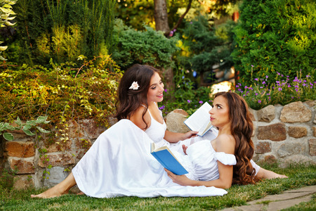 Two cute sisters reading a book while sitting lawn. Girls discuss the reading. Literary discussion. Poetry readings. They are in long white dresses. Stock Photo