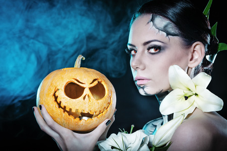 flower head: Young attractive girl with creative make-up for Halloween. Close-up portrait with a pumpkin. Mysterious image of lilies and red eyes. Jack-o-lantern Stock Photo