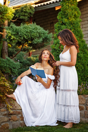 Two sisters. She reads a book, and her sister plait her braids. Girls in long white dresses.