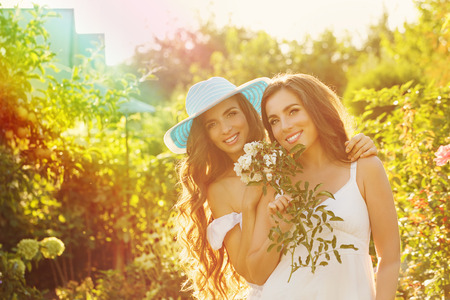 Two sisters. Girl holding a bouquet of flowers. Sister in the background embraces her. Family time. Human relationships. Stock Photo