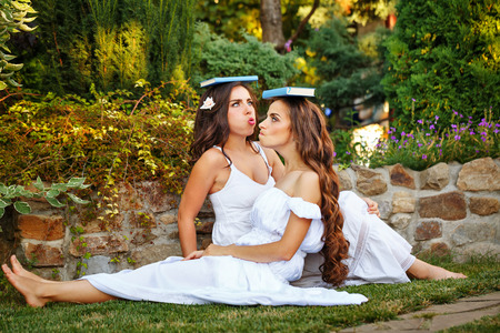Two cute sisters fooling around with books sitting on the lawn. Girls put books on his head and are posing funny face. Stock Photo
