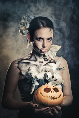dreadful: Young attractive girl with creative make-up for Halloween. Portrait close-up pumpkins. Mysterious and frightening image of lilies and red eyes. Witchcraft. Dreadful. Jack-o-lantern Stock Photo
