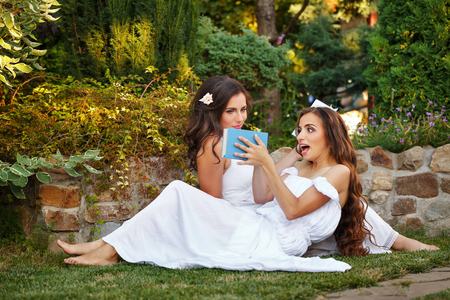 Two cute sisters reading books while sitting on the lawn. Girls discuss the reading. Literary discussion. Poetry readings. She slammed the book Stock Photo