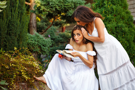 Two sisters. She reads a book while her sister kisses her on the top of the head. Girls in long white dresses. Family time in the backyard.