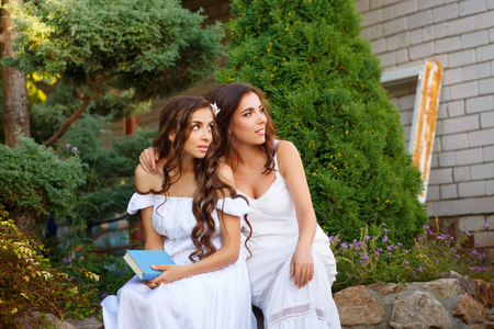 Two sisters. She holding a book, and sister hugging her. Girls in long white dress looks aside. Family time in the backyard.