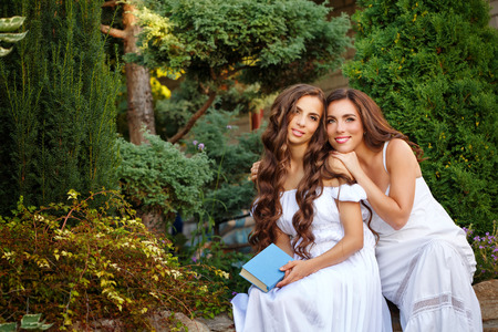 Two sisters. She holding a book, and sister hugging her. Girls in long white dresses. Family time in the backyard.